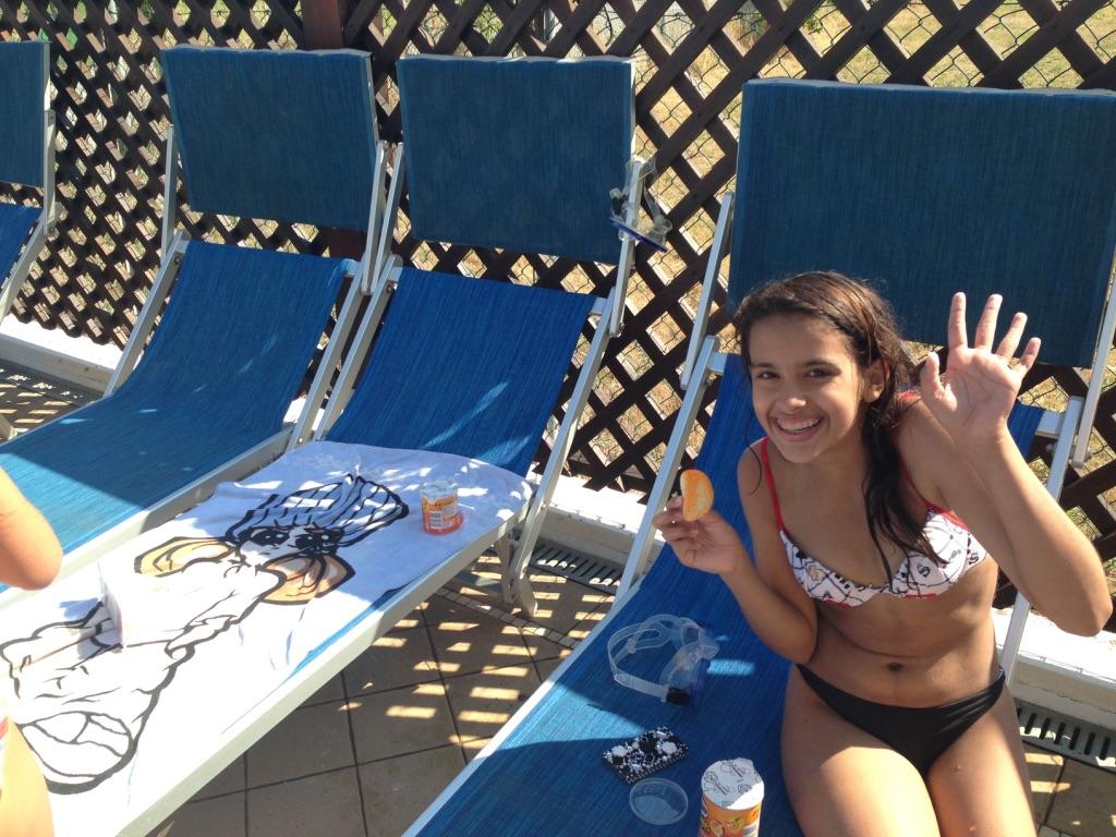 ragazzina saluta da lettino bordo piscina