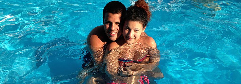 ragazzi piscina abbracciati sorridenti